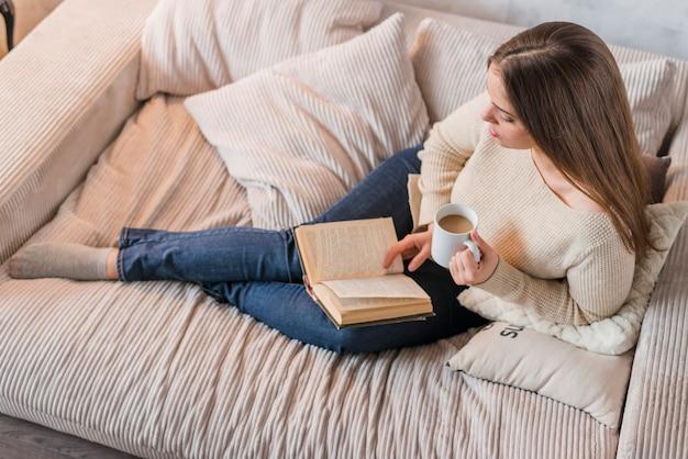 本を読んでのコーヒーのカップを保持している若い女性