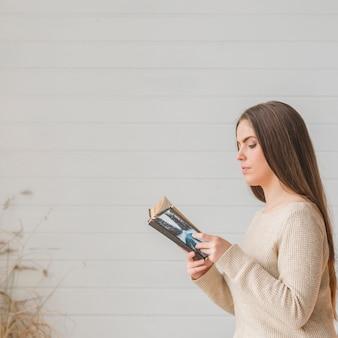 Крупным планом молодая женщина, чтение книги на белом фоне