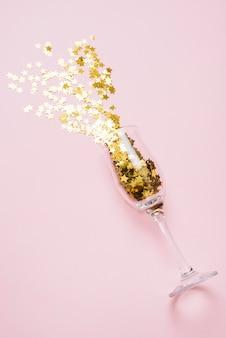 ピンクのテーブルの上にガラスから飛び散ったスタースパンコール