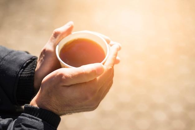 コーヒーカップを奪う人の手のクローズアップ