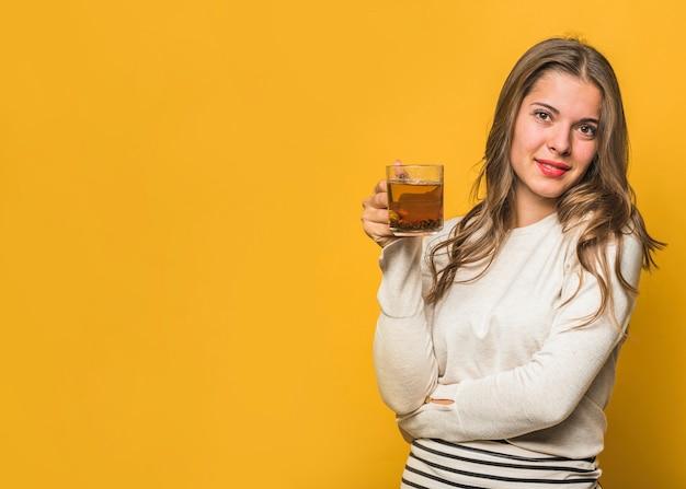 黄色の背景に対して手で立っているハーブティーのカップを保持している魅力的な若い女性