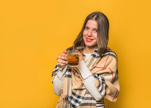 黄色の背景に対して手でハーブティーカップを保持している若い女性の笑みを浮かべてください。