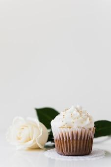 白いバラの白い背景で隔離のホイップクリームのカップケーキ