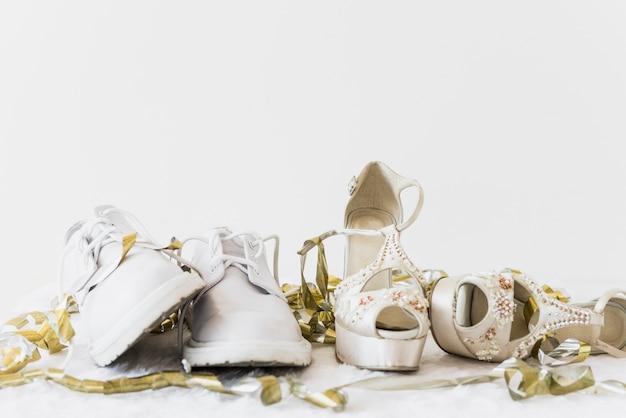 結婚式の白い靴と白い背景の上の黄金の吹流しと優雅なハイヒール
