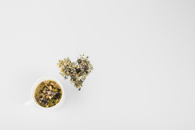 白い背景にお茶のカップの近くのハーブで作られたハート形