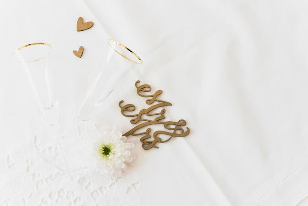 結婚式の単語の夫婦と花と夫人の平面図。白い表面にガラスとハートの形を飲む