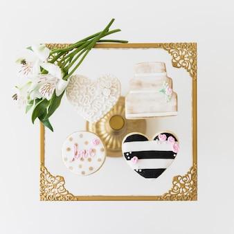 ガラステーブルの上の様々な形のクッキーとアルストロメリアの花の立面図