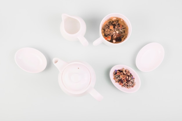 白い表面に食器の近くのお茶で乾燥ハーブのトップビュー