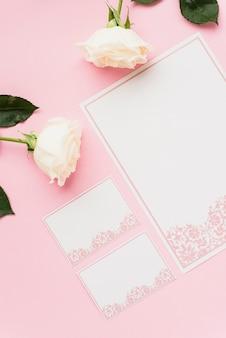 空白のカードとピンクの表面に白いバラの高角度のビュー