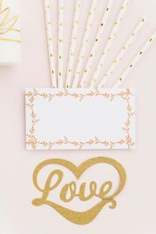 色付きの背景にストローと空白の白いカードを持つ愛のテキストの立面図