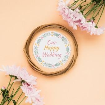 パステル調の背景に私たちの幸せな結婚式のテキストとピンクの花の円形フレームの高角度のビュー