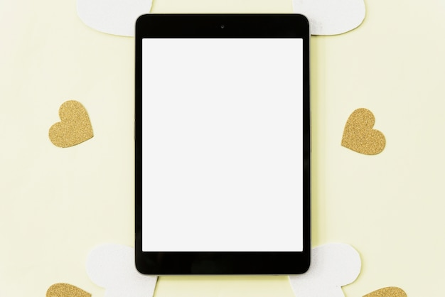 黄色の背景にハートのステッカーに囲まれたデジタルタブレットの立面図