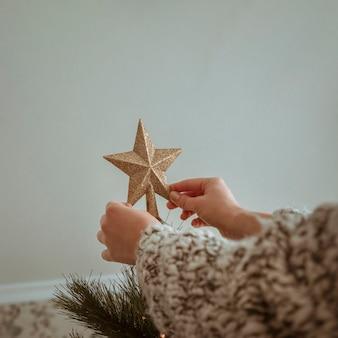 手はクリスマスツリーのための金色のトップスターを保持