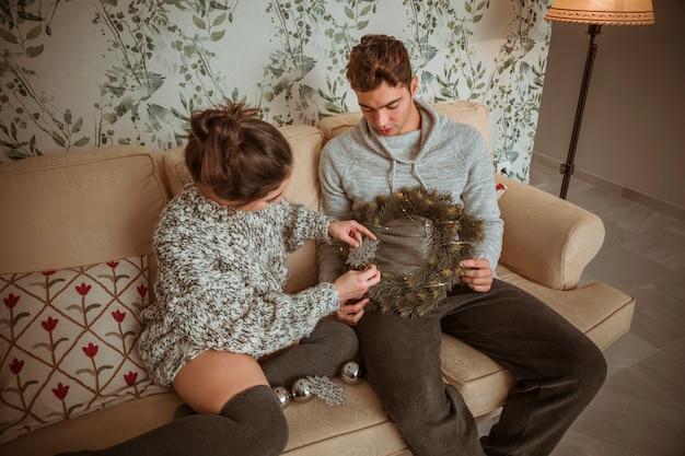 クリスマスの花輪を飾るソファに座ってカップル