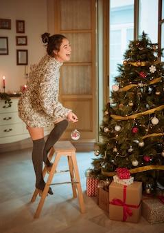 おもちゃでクリスマスツリーを飾る幸せな女性