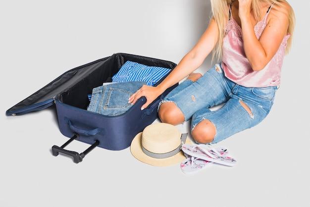 旅行のための女性梱包スーツケース