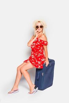 金髪の観光客がスーツケースでポーズ