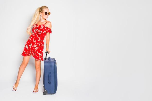 スーツケースを持つ金髪の女性