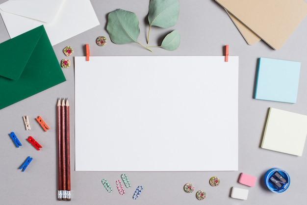 灰色の背景上の文房具に囲まれた衣服止め釘と空白の白いページ