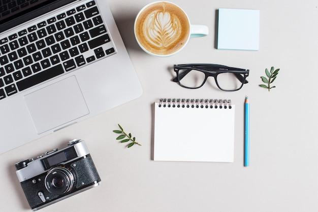 Чашка горячего кофе капучино латте арт; ноутбук и камера с канцелярскими принадлежностями на белом фоне