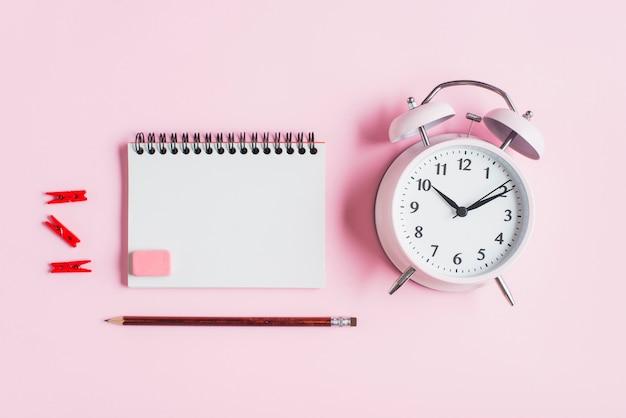 赤い洋服ペグ。スパイラルメモ帳。ゴム;ピンクの背景に対して鉛筆と目覚まし時計