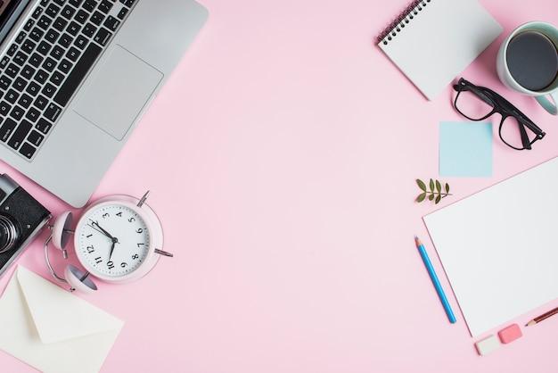 文房具ノートパソコンカメラ;エンベロープ;目覚まし時計とピンクの背景に文房具