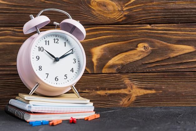 ノートブックと木製の壁紙に対して衣服止め釘の積み重ねの上のピンクの目覚まし時計