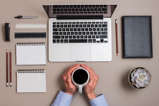 色付きの机の上の事務用品とラップトップとコーヒーカップを持っている手の俯瞰