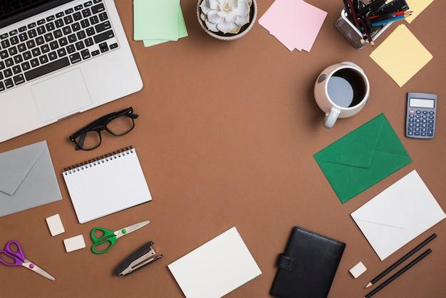 茶色のデスクトップ上の文房具とラップトップとコーヒーカップ