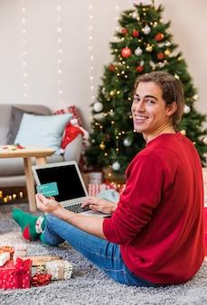 ラップトップでオンラインショッピングをする笑い男