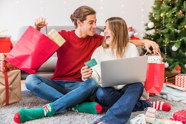 Возбужденный мужчина и женщина с покупками и ноутбуком