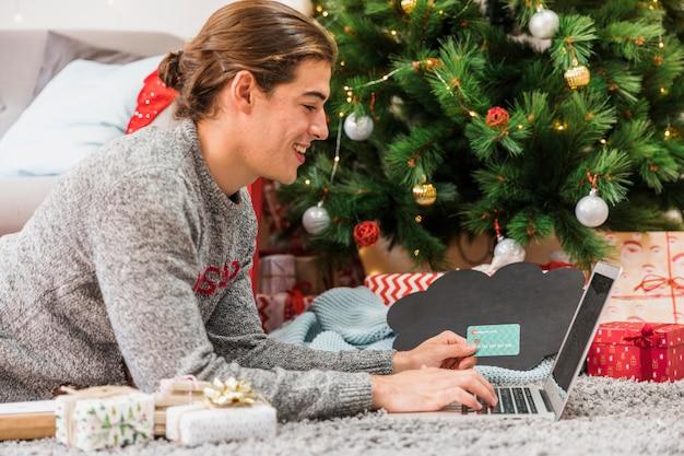 クリスマスショッピングをオンラインでやっている陽気な男