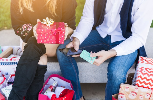 Пара, сидя с небольшой подарочной коробке на скамейке