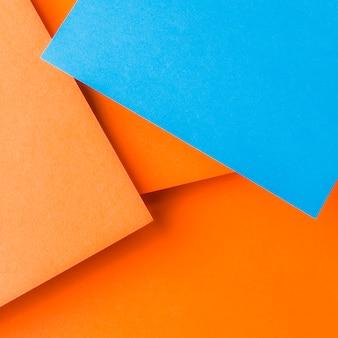 プレーンオレンジ色の背景上の青いクラフト紙の俯瞰