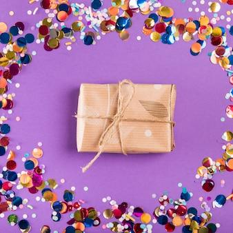 紫色の背景にカラフルな紙吹雪に囲まれたラップされたプレゼントの上に紐