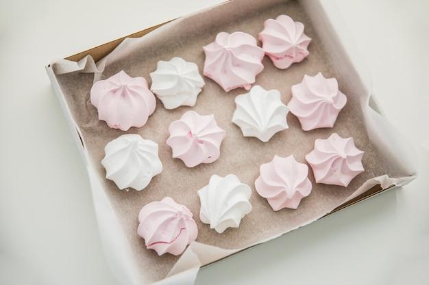 Вид сверху розовые и белые зефиры в коробке на белом фоне