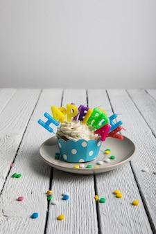 カラフルな誕生日の蝋燭そして木の織り目加工のテーブルの上のキャンディーのカップケーキ