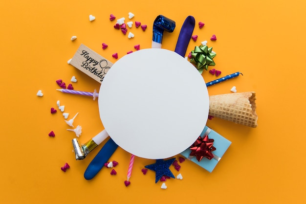 パーティーの送風機の上の白い空白の丸いフレーム。ギフト用の箱;ろうそくオレンジ色の背景に対して振りかけるとワッフルコーン