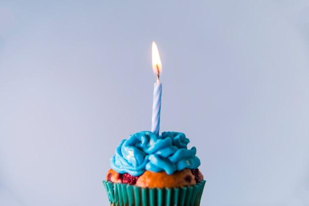 青い背景にカップケーキの上の単一のつけられた蝋燭