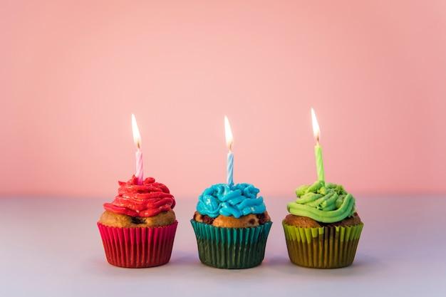 赤;ピンクの背景に対して火をつけたキャンドルで青と緑のカップケーキ