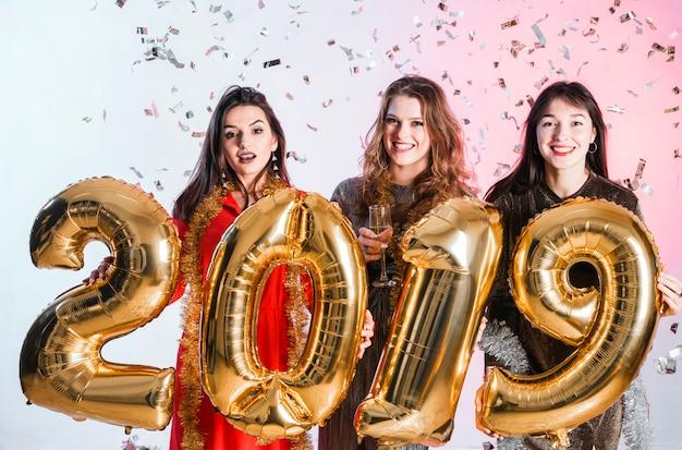 新年パーティーで金色の風船でポーズを取る女の子