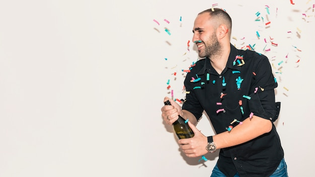 黒のシャンパンボトルを開いている男