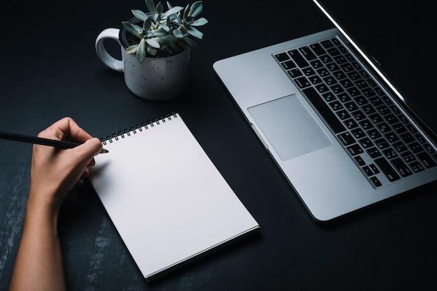 メモ帳とノートパソコンのコンセプト