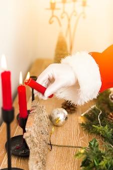サンタクロースがクリスマスキャンドルを照らす