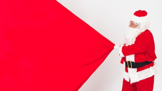 サンタクロースは、クリスマスバッグを引っ張って