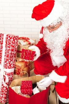 Санта-клаус ставит подарочные коробки в большой мешок