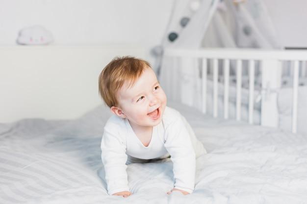 白いベッドでかわいいブロンドの赤ちゃん