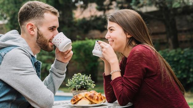 庭でコーヒーを飲む愛の若いカップル