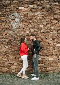 レンガの壁の前で愛している若いカップル