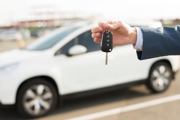 車の前に鍵を持つビジネスマン